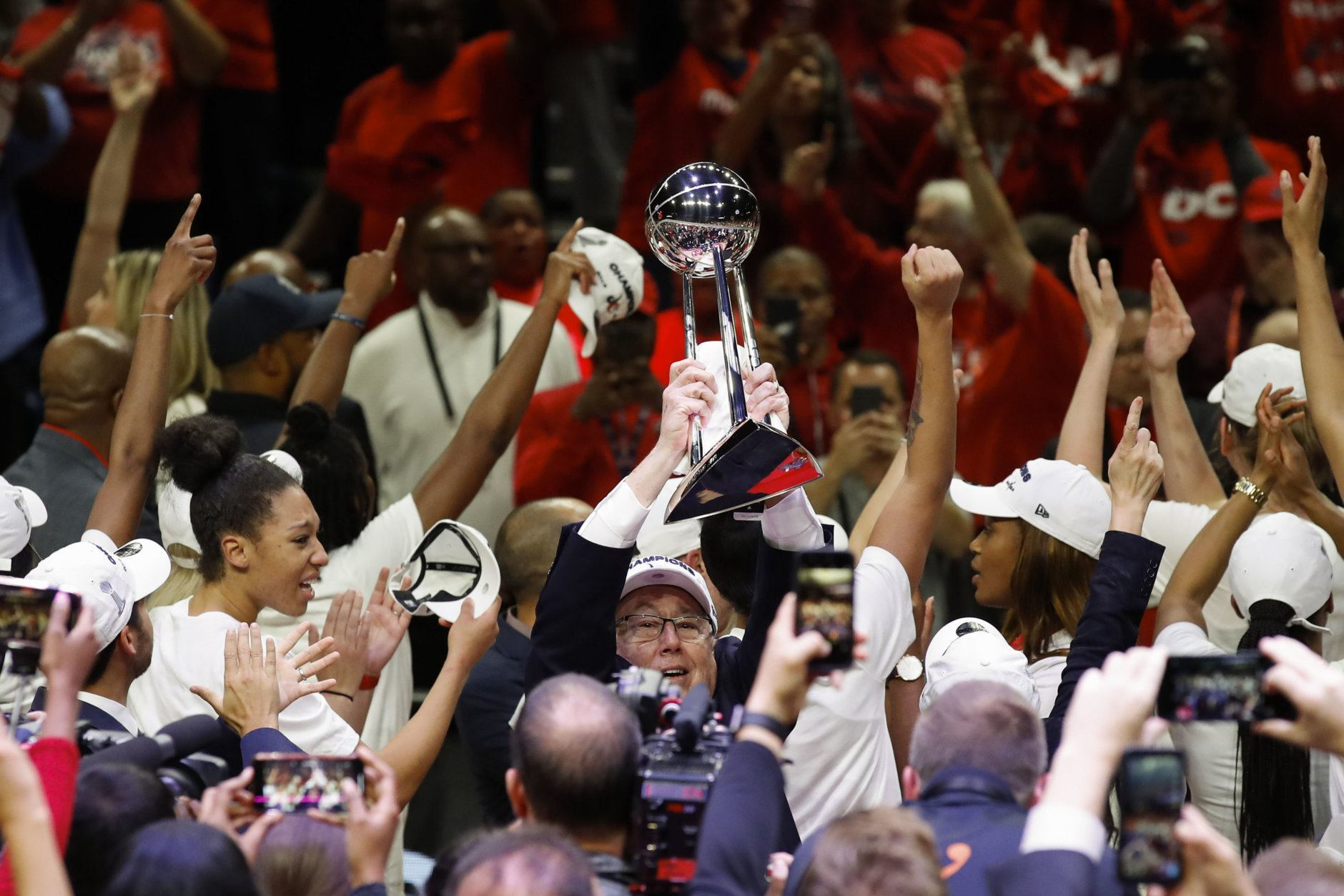 Washington Mystics head coach Mike Thibault holds up the trophy after Game 5 of basketball's WNBA Finals against the Connecticut Sun, Thursday, Oct. 10, 2019, in Washington. The Mystics won 89-78. (AP Photo/Alex Brandon)