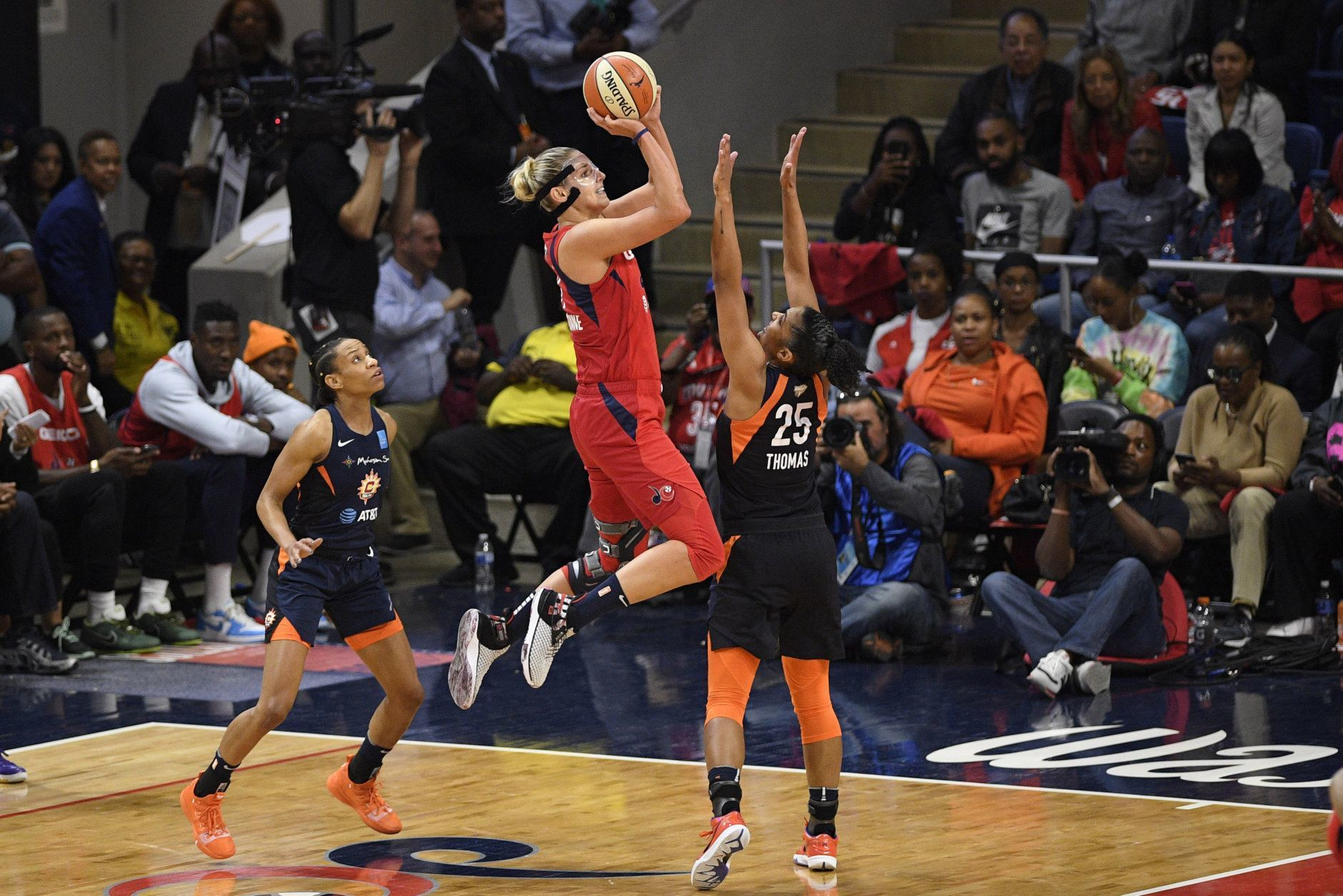 Washington Mystics forward Elena Delle Donne, center, shoots between Connecticut Sun guard Jasmine Thomas, left, and forward Alyssa Thomas (25) in the second half of Game 5 of basketball's WNBA Finals, Thursday, Oct. 10, 2019, in Washington. (AP Photo/Nick Wass)