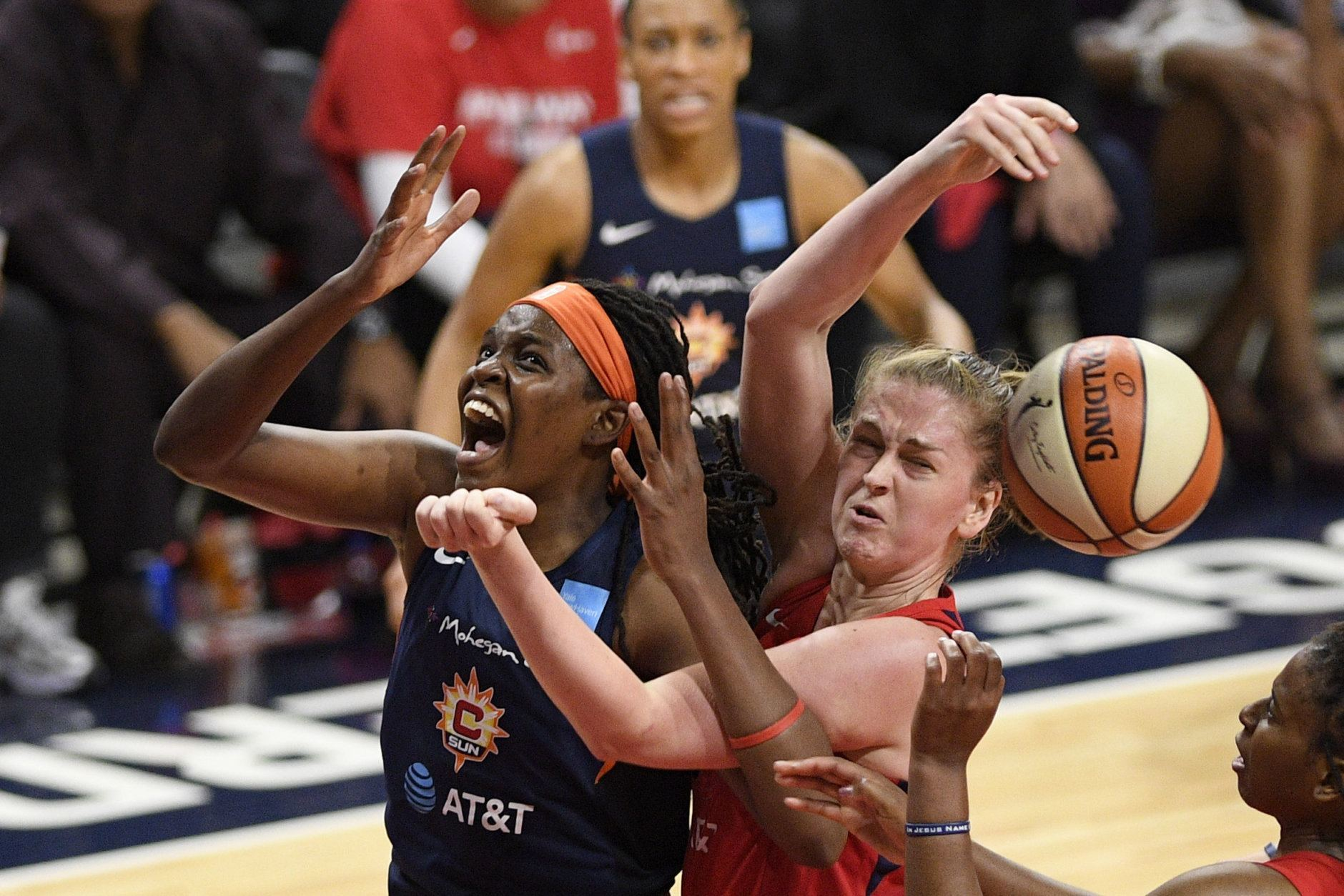 Connecticut Sun forward Jonquel Jones, left, battles for the ball against Washington Mystics center Emma Meesseman, right, in the second half of Game 5 of basketball's WNBA Finals, Thursday, Oct. 10, 2019, in Washington. (AP Photo/Nick Wass)