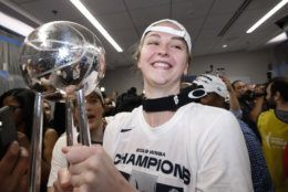 Washington Mystics center Emma Meesseman holds the trophy in the locker room after Game 5 of basketball's WNBA Finals against the Connecticut Sun, Thursday, Oct. 10, 2019 in Washington. (AP Photo/Alex Brandon)