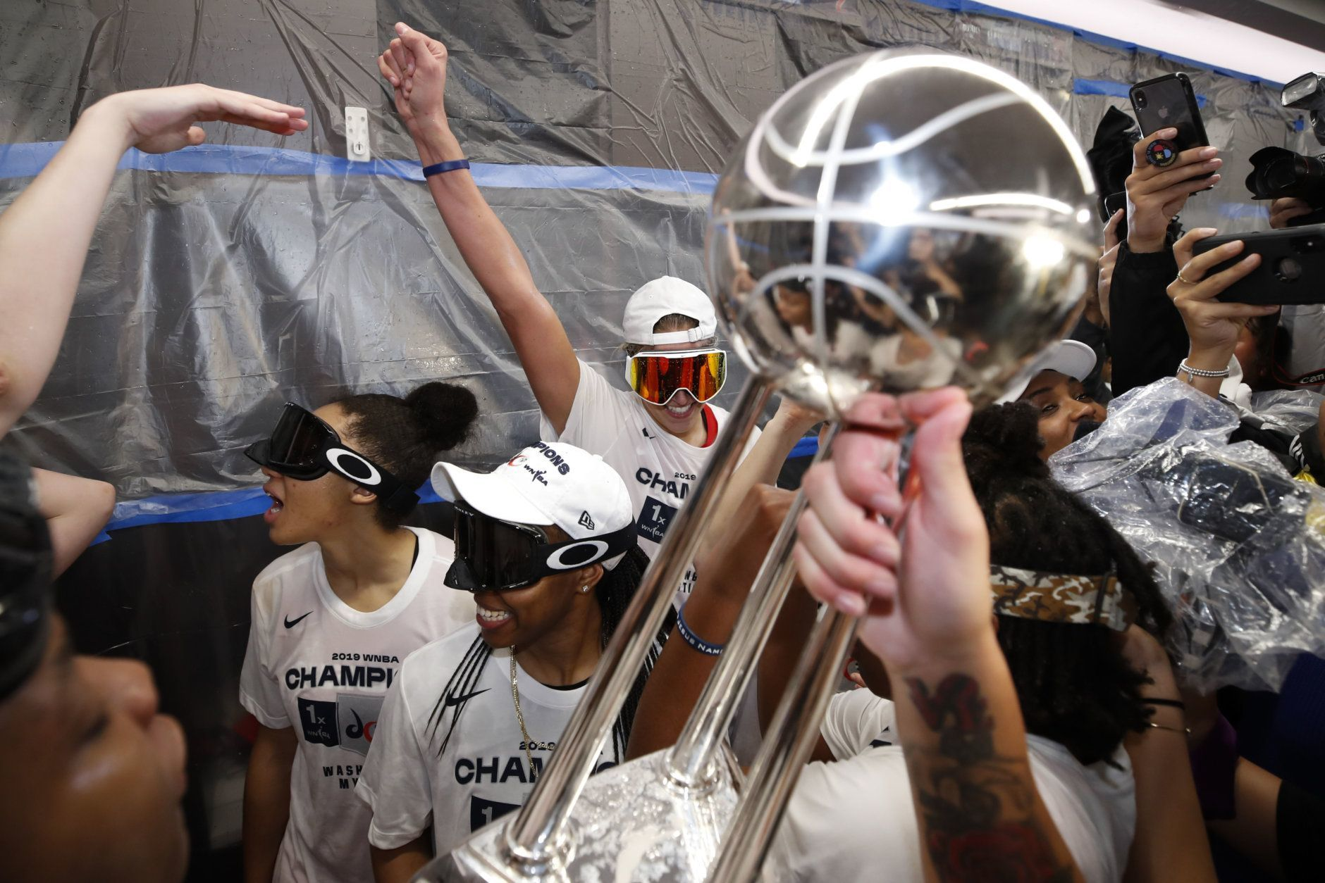 Washington Mystics forward Elena Delle Donne, back center, and others celebrate with the trophy in the locker room after Game 5 of basketball's WNBA Finals against the Connecticut Sun, Thursday, Oct. 10, 2019, in Washington. (AP Photo/Alex Brandon)