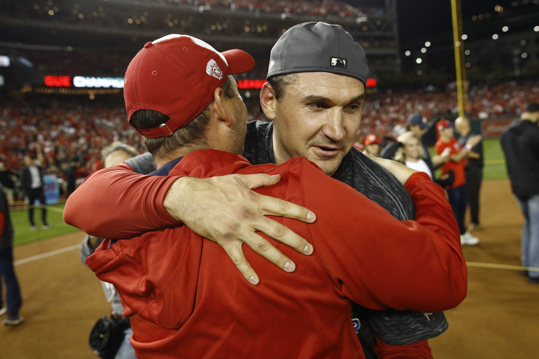 Washington Nationals manager Dave Martinez and Ryan Zimmerman celebrate after Game 4 of the baseball National League Championship Series against the St. Louis Cardinals Tuesday, Oct. 15, 2019, in Washington. The Nationals won 7-4 to win the series 4-0. (AP Photo/Patrick Semansky)