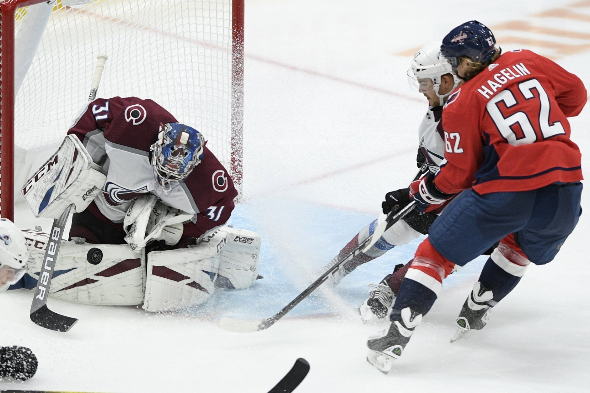 Colorado Avalanche goaltender Philipp Grubauer (31), of Germany, stops the puck in front of Washington Capitals left wing Carl Hagelin (62), of Sweden, during the third period of an NHL hockey game, Monday, Oct. 14, 2019, in Washington. (AP Photo/Nick Wass)