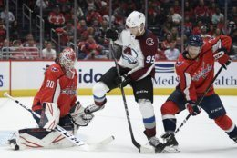 Colorado Avalanche left wing Andre Burakovsky (95) battles for the puck against Washington Capitals goaltender Ilya Samsonov (30), of Russia, and defenseman Nick Jensen (3) during the first period of an NHL hockey game, Monday, Oct. 14, 2019, in Washington. (AP Photo/Nick Wass)