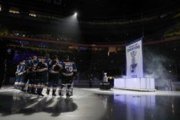 Members of the St. Louis Blues watch as the Stanley Cup championship banner is raised during a ceremony before the start of an NHL hockey game against the Washington Capitals Wednesday, Oct. 2, 2019, in St. Louis. The Blues defeated the Boston Bruins to with the Stanley Cup last season. (AP Photo/Jeff Roberson)