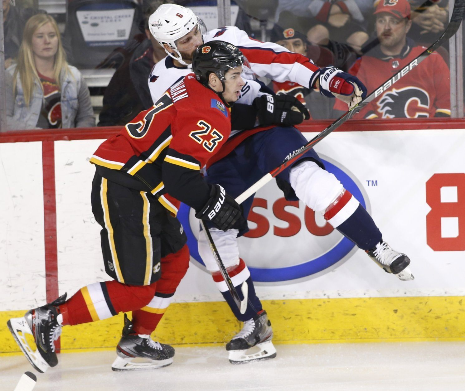 Washington Capitals' Michal Kempny, rear, from the Czech Republic, takes a hit from Calgary Flames' Sean Monahan during the first period of an NHL hockey game Tuesday, Oct. 22, 2019, in Calgary, Alberta. (Larry MacDougal/The Canadian Press via AP)