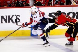 Washington Capitals center Evgeny Kuznetsov (92) moves the puck up ice as Calgary Flames centre Derek Ryan (10) defends during the second period of an NHL hockey game Tuesday, Oct. 22, 2019, in Calgary, Alberta. (Larry MacDougal/The Canadian Press via AP)
