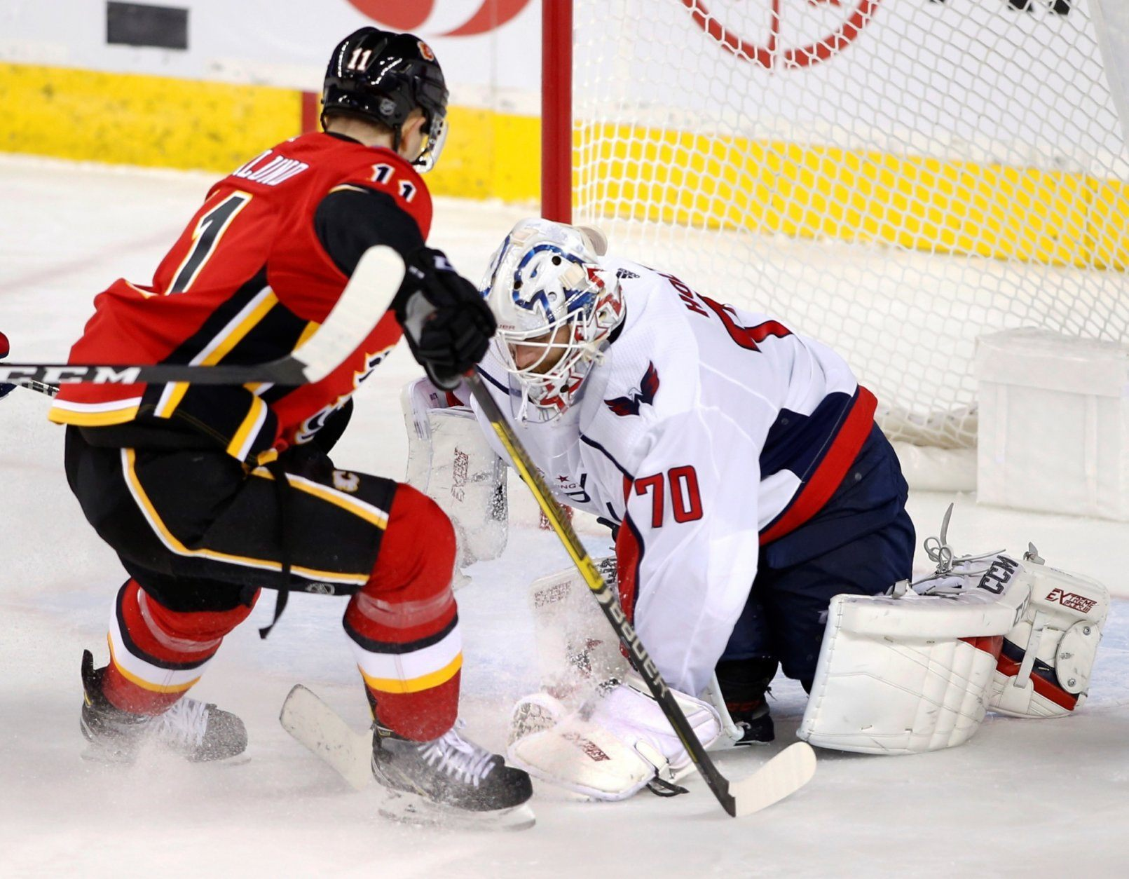Washington Capitals goaltender Braden Holtby (70) stops the puck as Calgary Flames center Mikael Backlund (11) looks for a rebound during the second period of an NHL hockey game Tuesday, Oct. 22, 2019, in Calgary, Alberta. (Larry MacDougal/The Canadian Press via AP)