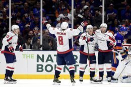 Washington Capitals right wing T.J. Oshie (77) is congratulated by teammates, including left wing Alex Ovechkin (8), center Nicklas Backstrom (19) and left wing Jakub Vrana (13), after scoring a goal against the New York Islanders during the second period of an NHL hockey game, Friday, Oct. 4, 2019, in Uniondale, N.Y. (AP Photo/Steven Ryan)