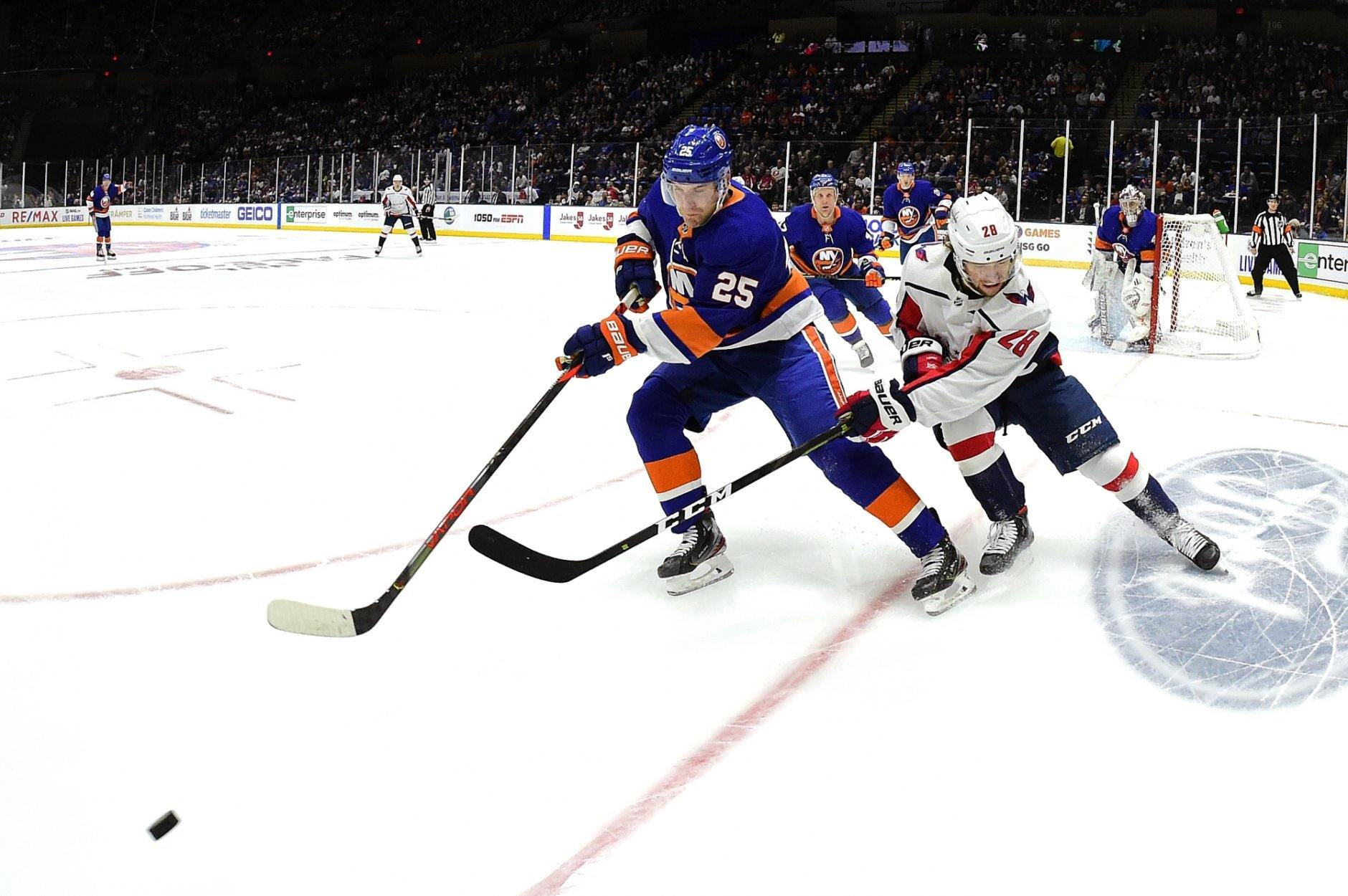 New York Islanders defenseman Devon Toews (25) is defended by Washington Capitals left wing Brendan Leipsic (28) during the first period of an NHL hockey game, Friday, Oct. 4, 2019, in Uniondale, N.Y. (AP Photo/Steven Ryan)