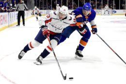 Washington Capitals left wing Jakub Vrana (13) and New York Islanders defenseman Scott Mayfield (24) chase down the puck during the first period of an NHL hockey game, Friday, Oct. 4, 2019, in Uniondale, N.Y. (AP Photo/Steven Ryan)