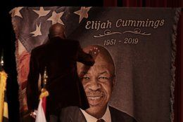 Norris Davis, friend of the late U.S. Rep. Elijah Cummings, touches a banner with the likeness of the congressman after speaking during a viewing service at Morgan State University, Wednesday, Oct. 23, 2019, in Baltimore. The Maryland congressman and civil rights champion died Thursday, Oct. 17, at age 68 of complications from long-standing health issues. (AP Photo/Julio Cortez)