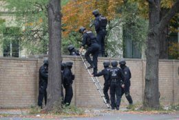Police officers cross a wall at a crime scene in Halle, Germany, Wednesday, Oct. 9, 2019. A gunman fired several shots on Wednesday in the German city of Halle. Police say a person has been arrested after a shooting that left two people dead. (Sebastian Willnow/dpa via AP)