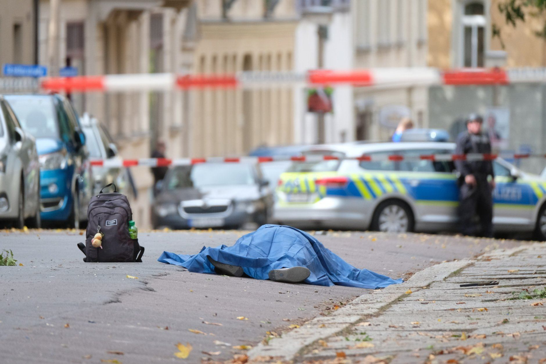 A person lies on a road in Halle, Germany, Wednesday, Oct. 9, 2019. A gunman fired several shots on Wednesday in German city of Halle and at least two got killed, according to local media FOCUS online. The gunman is on the run and police have sealed off the surrounding area. (Sebastian Willnow/dpa via AP)