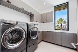 This photo provided by interior designer Raquel Mothe of Mothe Design shows a laundry room designed by Mothe in Fort Lauderdale, Fla. This laundry room includes plenty of storage with cabinets by Ornare, as well as recessed ceiling lighting and natural light, creating a space that's welcoming and also functional. (Mothe Design via AP)