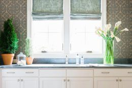 This undated photo provided by interior designer Brian Patrick Flynn shows a laundry room designed by Flynn. For this laundry room Flynn used a chandelier and patterned wallpaper to create a warm, inviting space. (Robert Peterson/Rustic White Photography/Brian Patrick Flynn via AP)