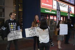 Activists hold signs outside Capital One Arena before an NBA preseason basketball game between the Washington Wizards and the Guangzhou Loong-Lions, Wednesday, Oct. 9, 2019, in Washington. (AP Photo/Nick Wass)