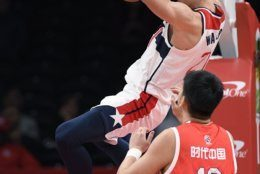 Washington Wizards center Moritz Wagner, top, dunks against Guangzhou Loong-Lions center Mingyang Sun during the first half of an NBA exhibition basketball game Wednesday, Oct. 9, 2019, in Washington. (AP Photo/Nick Wass)