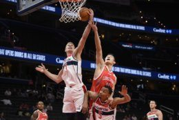 Washington Wizards center Moritz Wagner (21) and guard Justin Robinson (5) vie for the ball against Guangzhou Loong-Lions forward Kai Guo (14) during the first half of an NBA exhibition basketball game Wednesday, Oct. 9, 2019, in Washington. (AP Photo/Nick Wass)