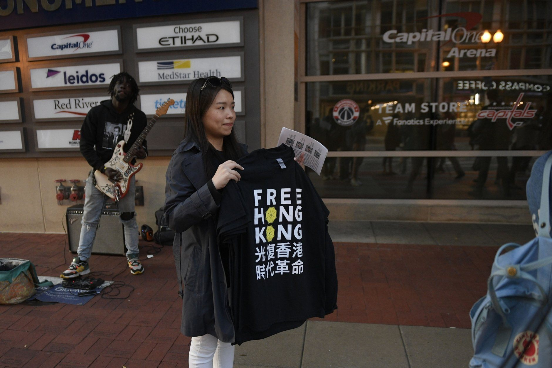 An activist stands outside Capital One Arena before an NBA exhibition basketball game between the Washington Wizards and the Guangzhou Loong-Lions, Wednesday, Oct. 9, 2019, in Washington. (AP Photo/Nick Wass)