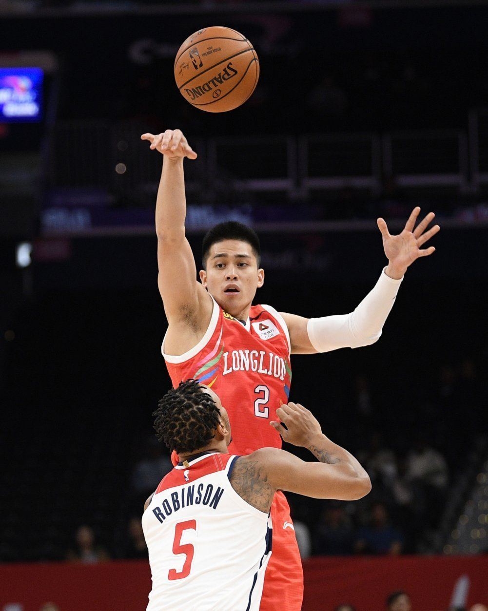 Guangzhou Loong-Lions guard Ying-Chun Chen (2) passes the ball over Washington Wizards guard Justin Robinson (5) during the first half of an NBA exhibition basketball game, Wednesday, Oct. 9, 2019, in Washington. (AP Photo/Nick Wass)