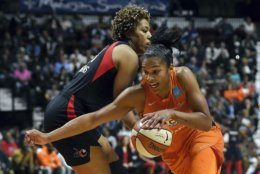 Connecticut Sun's Alyssa Thomas, front, drives past Washington Mystics' Tianna Hawkins during the first half in Game 4 of basketball's WNBA Finals, Tuesday, Oct. 8, 2019, in Uncasville, Conn. (AP Photo/Jessica Hill)