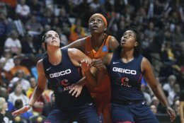Connecticut Sun's Jonquel Jones, center, fights for position under the basket between Washington Mystics' Elena Delle Donne, left, and Ariel Atkins, ritht, during the first half in Game 4 of basketball's WNBA Finals, Tuesday, Oct. 8, 2019, in Uncasville, Conn. (AP Photo/Jessica Hill)