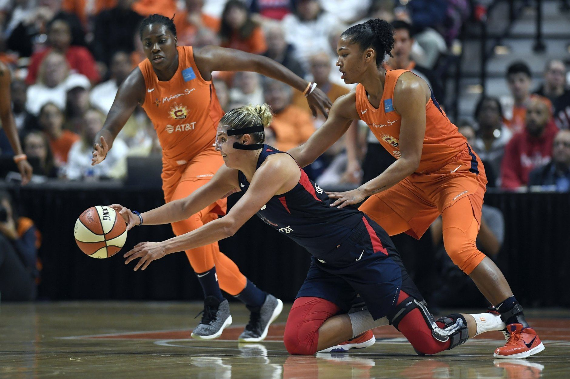 Washington Mystics' Elena Delle Donne, center, passes the ball between Connecticut Sun's Shekinna Stricklen, left, and Alyssa Thomas, right, during the first half in Game 3 of basketball's WNBA Finals, Sunday, Oct. 6, 2019, in Uncasville, Conn. (AP Photo/Jessica Hill)