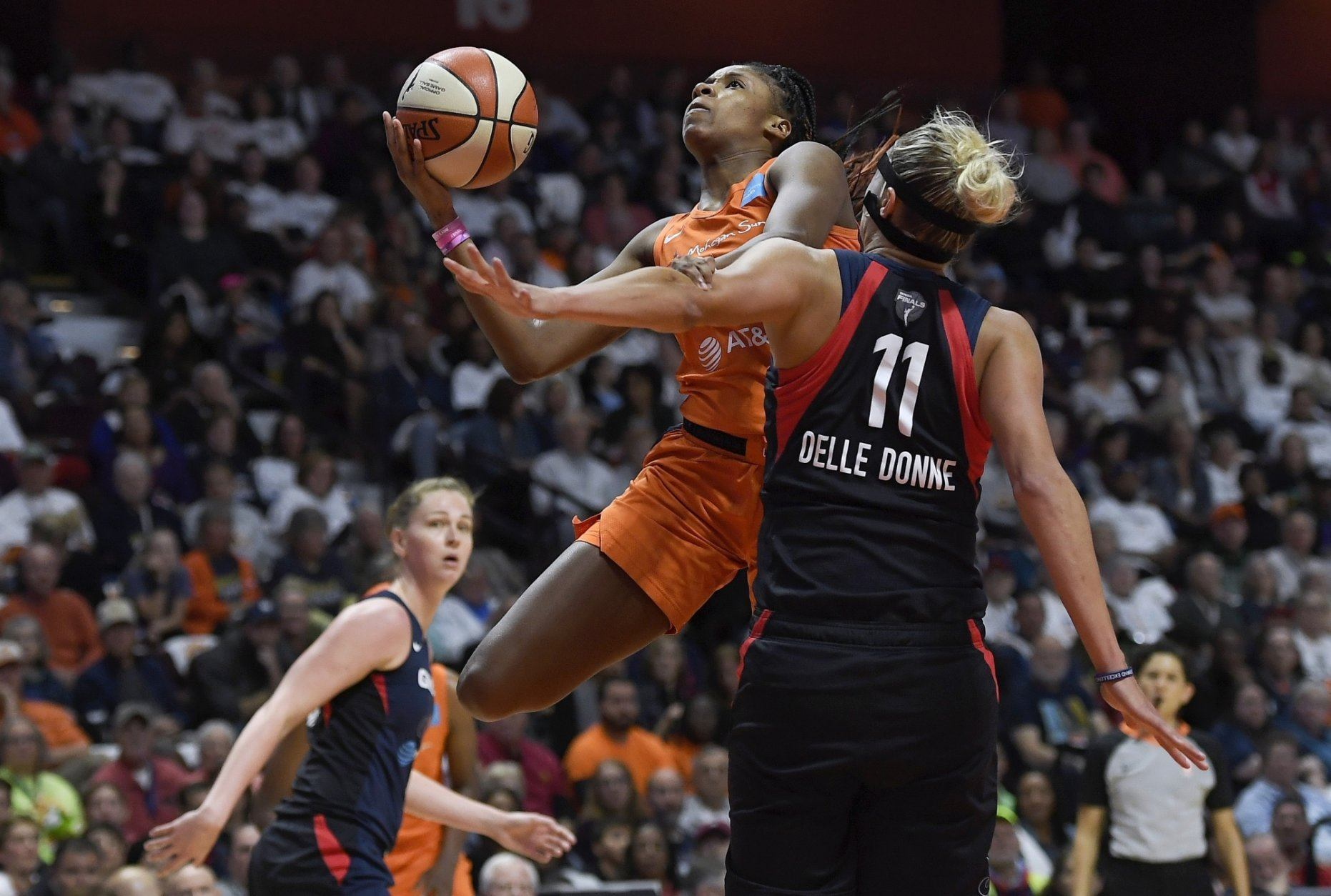 Connecticut Sun's Bria Holmes, rear, drives against Washington Mystics' Elena Delle Donne during the first half in Game 3 of basketball's WNBA Finals, Sunday, Oct. 6, 2019, in Uncasville, Conn. (AP Photo/Jessica Hill)