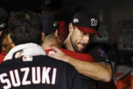 Washington Nationals starting pitcher Max Scherzer (31) is greeted by teammates in the dugout in the middle of the seventh inning in Game 4 of a baseball National League Division Series against the Los Angeles Dodgers, Monday, Oct. 7, 2019, in Washington. (AP Photo/Alex Brandon)