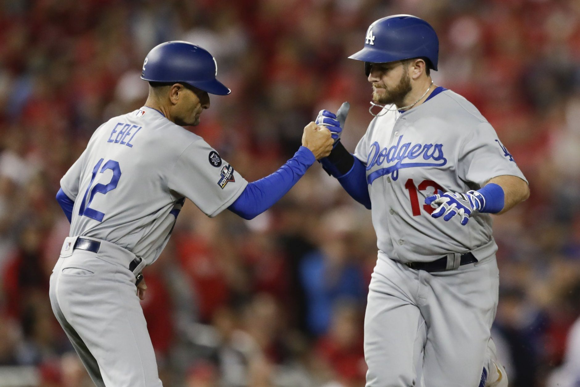 Los Angeles Dodgers first baseman Max Muncy celebrates his solo home run off Washington Nationals starting pitcher Anibal Sanchez with third base coach Dino Ebel (12) during the fifth inning in Game 3 of a baseball National League Division Series on Sunday, Oct. 6, 2019, in Washington. (AP Photo/Julio Cortez)