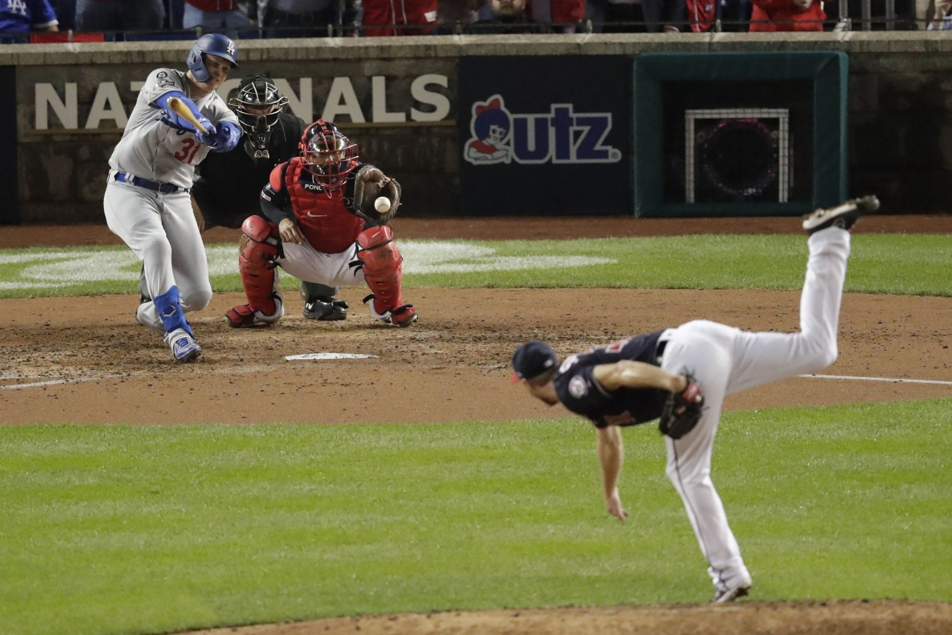 Los Angeles Dodgers' Joc Pederson, back left, strikes out swinging against Washington Nationals starting pitcher Max Scherzer, right, during the fifth inning in Game 4 of a baseball National League Division Series, Monday, Oct. 7, 2019, in Washington. Nationals catcher Kurt Suzuki, back right, and umpire Doug Eddings, back center, look on. (AP Photo/Julio Cortez)