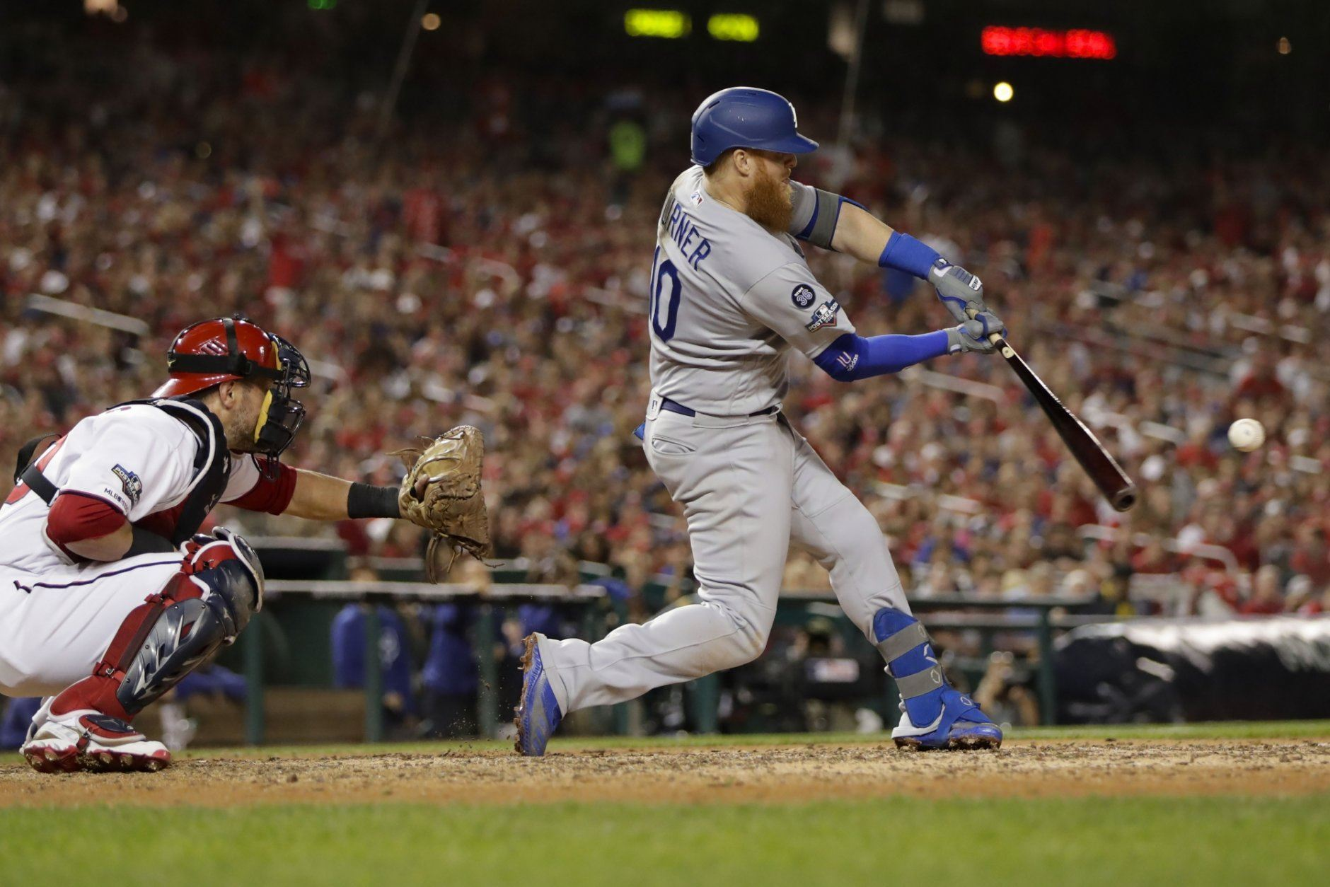 Los Angeles Dodgers third baseman Justin Turner (10) hits a three-run home run off Washington Nationals relief pitcher Wander Suero during the sixth inning in Game 3 of a baseball National League Division Series on Sunday, Oct. 6, 2019, in Washington. Behind the plate is Nationals catcher Kurt Suzuki. (AP Photo/Julio Cortez)
