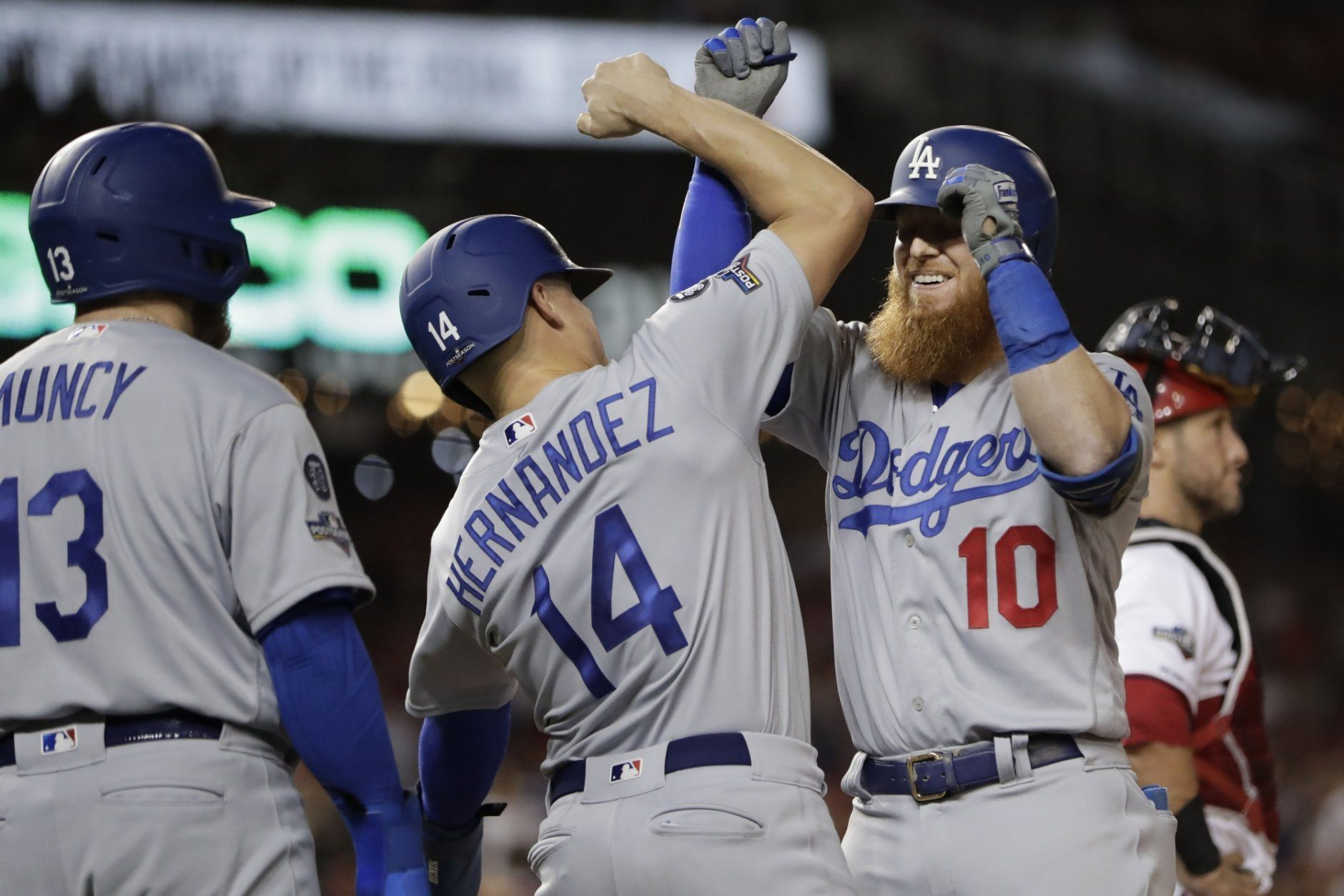 Los Angeles Dodgers third baseman Justin Turner (10) celebrates his three-run home run off Washington Nationals relief pitcher Wander Suero with teammates Enrique Hernandez (14) and Max Muncy (13) during the sixth inning in Game 3 of a baseball National League Division Series on Sunday, Oct. 6, 2019, in Washington. (AP Photo/Julio Cortez)