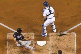 Washington Nationals' Adam Eaton, left, scores past Los Angeles Dodgers catcher Will Smith on a double by Anthony Rendon during the second inning in Game 2 of a baseball National League Division Series on Friday, Oct. 4, 2019, in Los Angeles. (AP Photo/Mark J. Terrill)