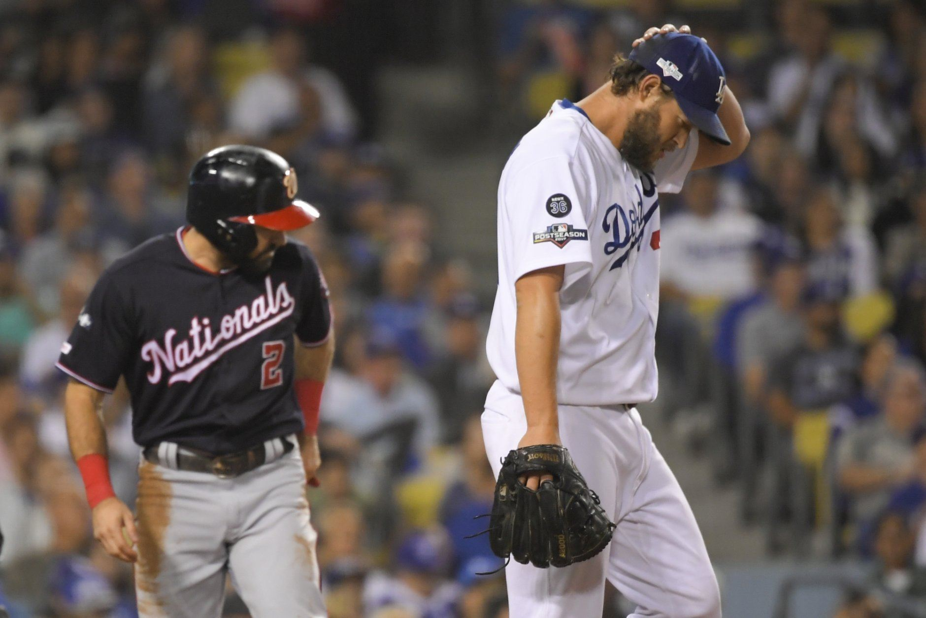 Washington Nationals' Adam Eaton, left, scores past Los Angeles Dodgers starting pitcher Clayton Kershaw on a double by Anthony Rendon during the second inning in Game 2 of baseball's National League Division Series against the Los Angeles Dodgers on Friday, Oct. 4, 2019, in Los Angeles. (AP Photo/Mark J. Terrill)