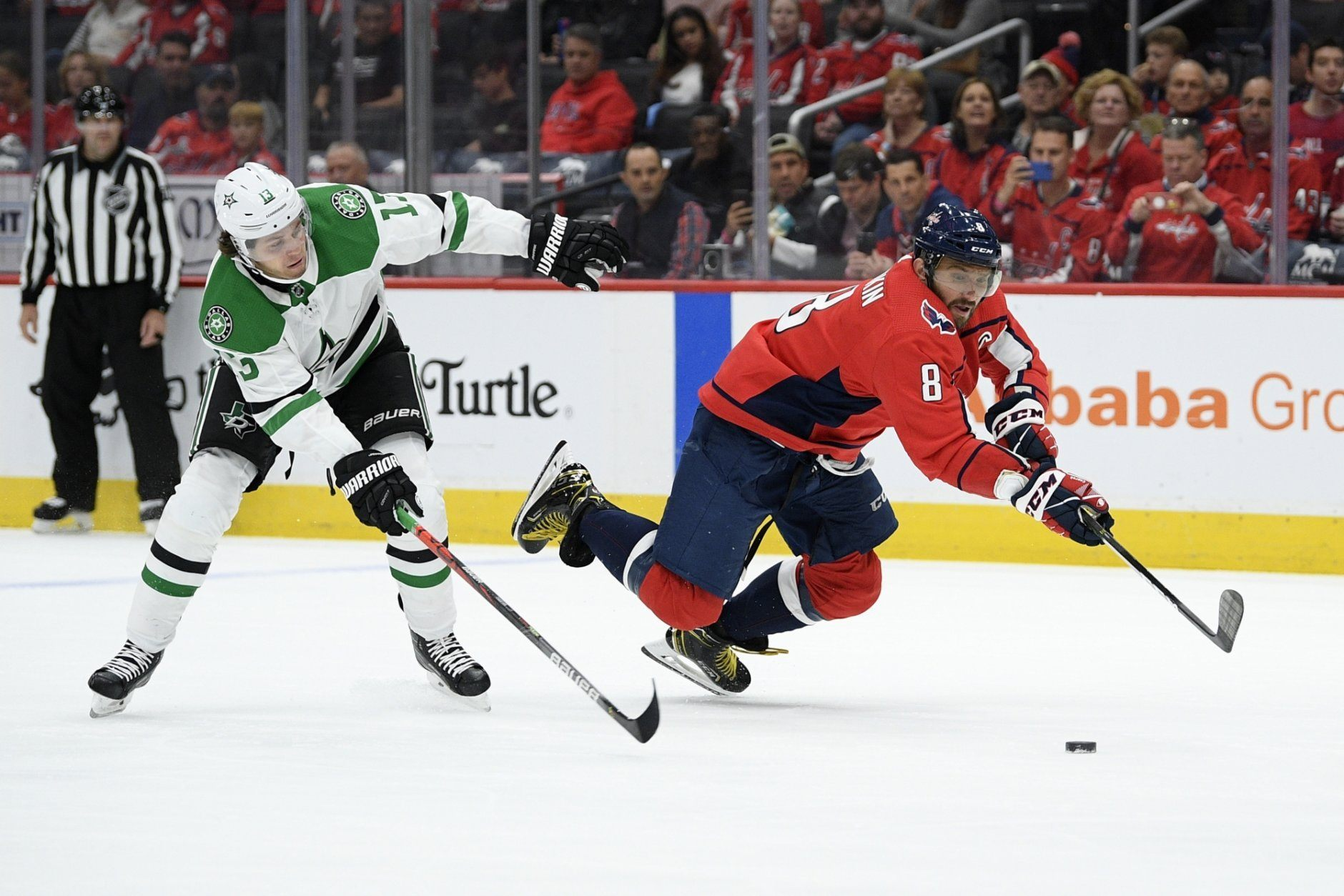 Washington Capitals left wing Alex Ovechkin (8), of Russia, scrambles for the puck in front of Dallas Stars center Mattias Janmark (13), of Sweden, during the first period of an NHL hockey game Tuesday, Oct. 8, 2019, in Washington. The Stars won 4-3 in overtime. (AP Photo/Nick Wass)