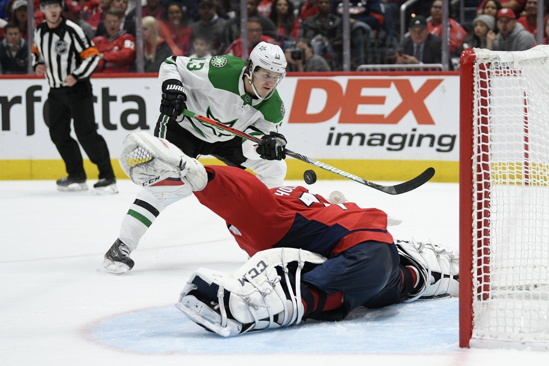 Washington Capitals goaltender Braden Holtby, bottom, stops the puck against Dallas Stars center Mattias Janmark (13), of Sweden, during the second period of an NHL hockey game Tuesday, Oct. 8, 2019, in Washington. (AP Photo/Nick Wass)