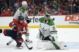 Washington Capitals left wing Brendan Leipsic (28) falls to the ice in front of Dallas Stars goaltender Ben Bishop (30) and defenseman John Klingberg (3) during the first period of an NHL hockey game Tuesday, Oct. 8, 2019, in Washington. (AP Photo/Nick Wass)