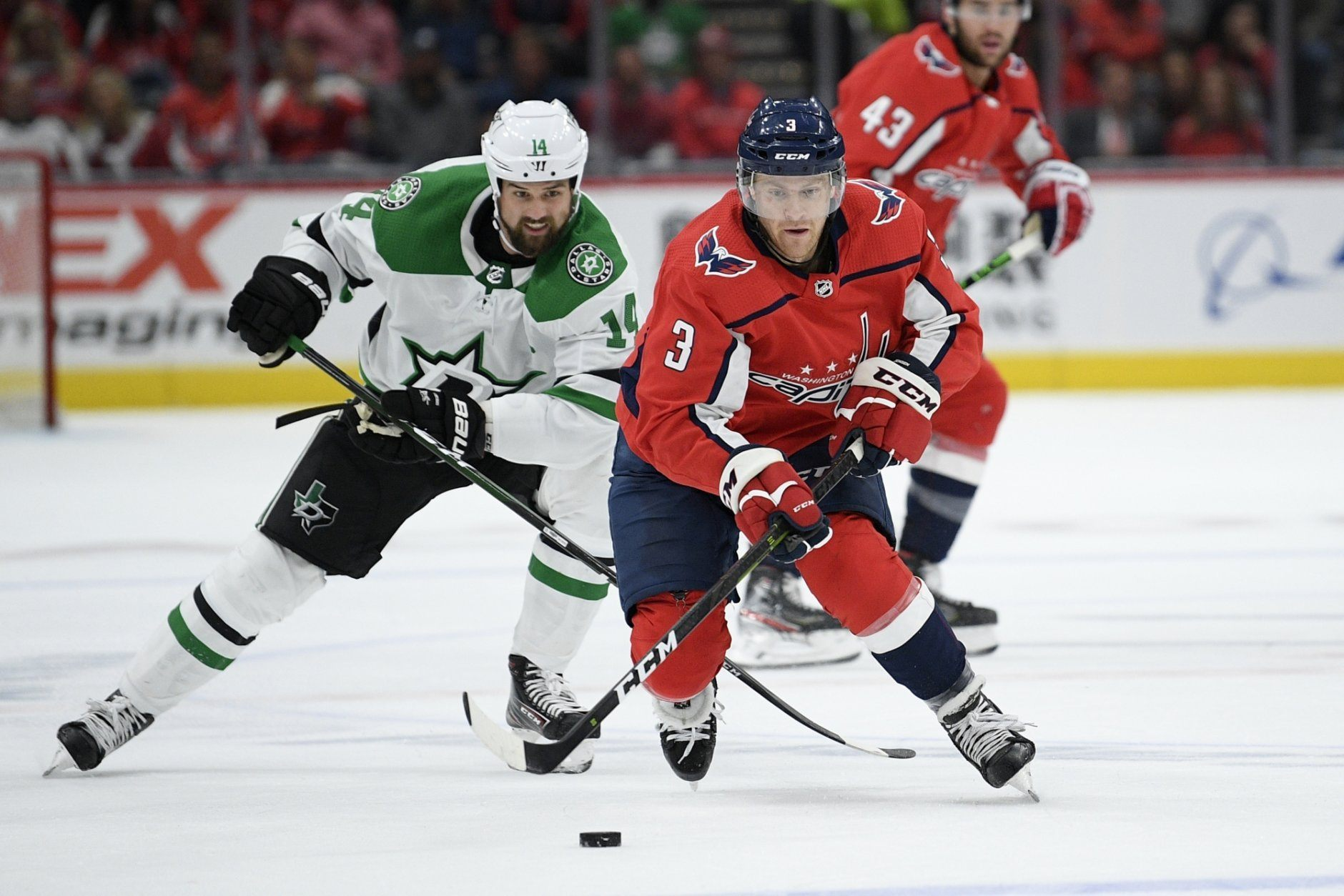 Washington Capitals defenseman Nick Jensen (3) skates with the puck next to Dallas Stars left wing Jamie Benn (14) during the second period of an NHL hockey game Tuesday, Oct. 8, 2019, in Washington. (AP Photo/Nick Wass)