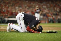 Washington Nationals' Trea Turner falls to the ground after getting hit with foul ball during the inning of Game 3 of the baseball World Series against the Houston Astros Friday, Oct. 25, 2019, in Washington. (AP Photo/Jeff Roberson)