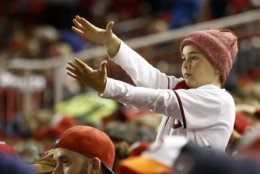 A fan gestures the baby shark as Washington Nationals' Gerardo Parra bats during the sixth inning of Game 3 of the baseball World Series Houston Astros Friday, Oct. 25, 2019, in Washington. (AP Photo/Patrick Semansky)