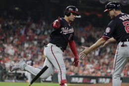 Washington Nationals' Juan Soto flips his bat as he is congratulated by first base coach Tim Bogar after hitting a home run during the sixth inning of Game 6 of the baseball World Series against the Houston Astros Tuesday, Oct. 29, 2019, in Houston. (AP Photo/David J. Phillip)