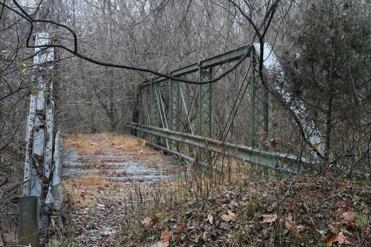 """<p>The remains of another centenarian structure can be found in rural Prince William County, Virginia.</p> <p>In 1900, a steel truss bridge was erected over Cedar Run south of Aden. The 87-foot timber-planked bridge carried Fleetwood Drive over the creek for most of the 20th century.</p> <p>Virginia Department of Transportation records indicate that the bridge was taken out of service in 1991 when it was replaced by a new two-lane bridge downstream. The state offered the bridge to any private parties that would relocate it. VDOT entered into an agreement with an interested party who planned to move the <a href=""""http://www.historicprincewilliam.org/county-history/structures/cedar-run-truss-bridge.html"""" target=""""_blank"""" rel=""""noopener"""">bridge to the base of the Old Rag Mountain</a>, but the deal later fell apart.</p>"""
