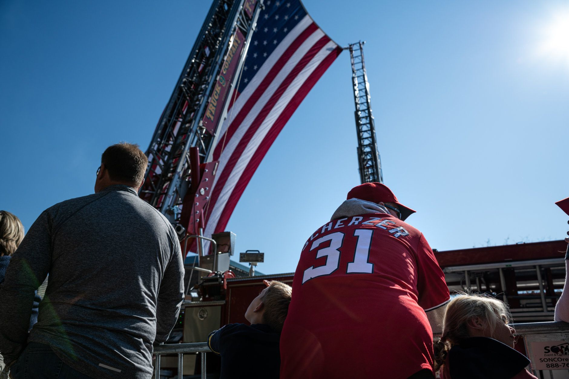 A Washington Nationals fan awaits the start of the parade on Constitution Avenue, beneath a behemoth American flag hoisted by two D.C. fire engines. (WTOP/Alejandro Alvarez)