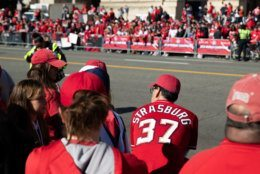 Nationals fans mingle along Constitution Avenue an hour prior to the beginning of the parade on a cold but sunny fall afternoon in downtown D.C. (WTOP/Alejandro Alvarez)