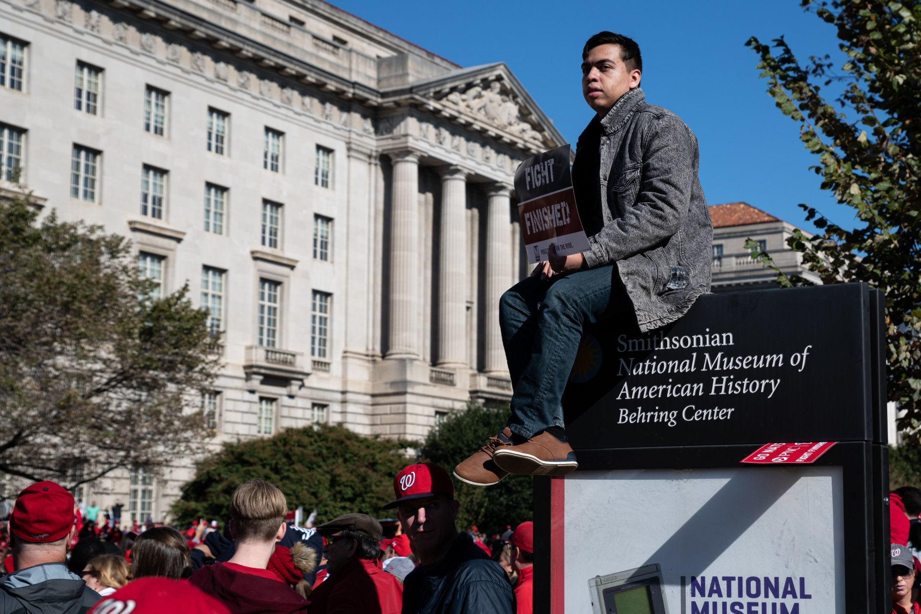 A Nationals fan sits atop a sign for the Smithsonian Museum of American History on Constitution Avenue. Fans mounted signs, ledges, power boxes and, on occassion, climbed street lights for a view above the dense crowd. (WTOP/Alejandro Alvarez)