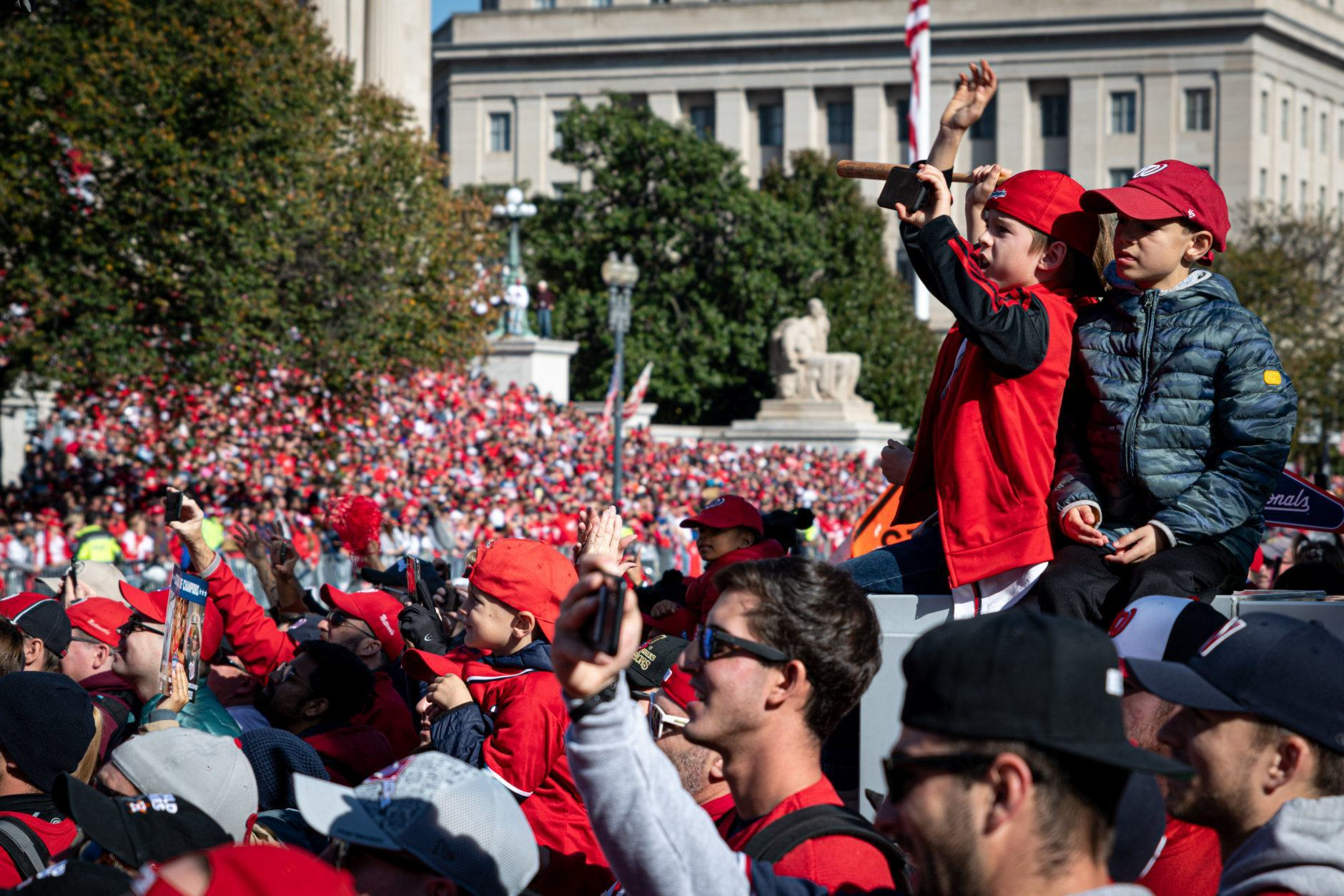 A group of children cheer the Nationals on their victory lap through Washington near the National Archives on Constitution Avenue. (WTOP/Alejandro Alvarez)