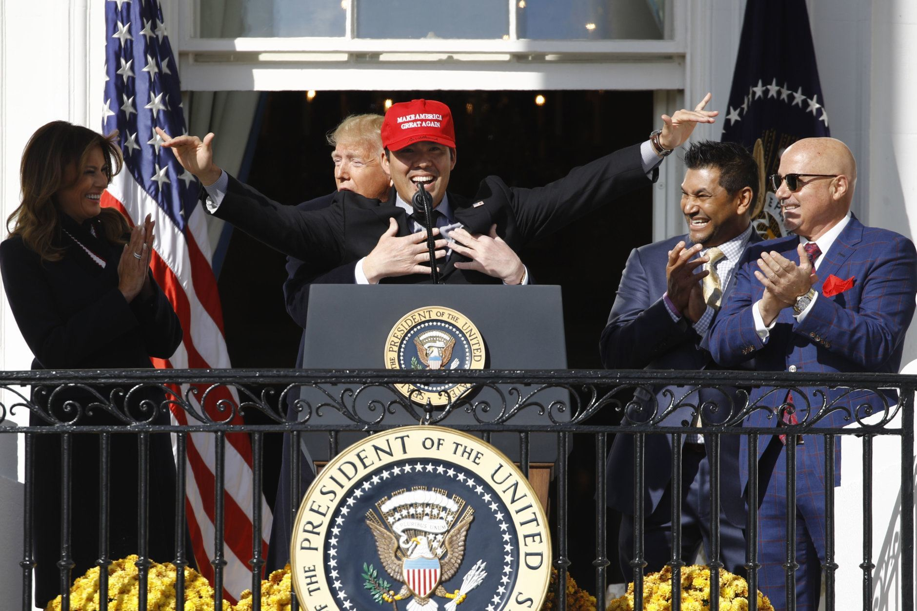 President Donald Trump hugs Washington Nationals catcher Kurt Suzuki, during an event to honor the 2019 World Series champion Washington Nationals on the balcony of the White House, Monday, Nov. 4, 2019, in Washington, as First Lady Melania Trump, left, and Washington Nationals coach Dave Martinez, second from right and general manager Mike Rizzo, far right, look on. Suzuki is wearing a Make America Great Again hat. (AP Photo/Patrick Semansky)