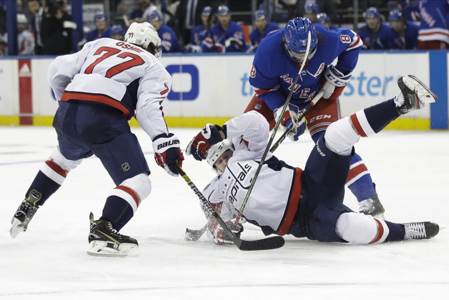 New York Rangers' Jacob Trouba (8) checks Washington Capitals' Jakub Vrana (13) as T.J. Oshie (77) watches during the second period of an NHL hockey game Wednesday, Nov. 20, 2019, in New York. (AP Photo/Frank Franklin II)